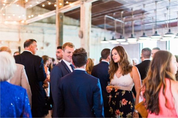 Journeyman Distillery Wedding by Tifani Lyn Photography // cocktail hour // Industrial warehouse wedding venue located in Three Oaks, Michigan ( West Michigan ). The venue features hardwood floors, brick, rustic metal and string lights galore.